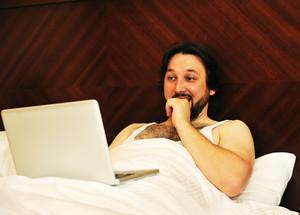 Man on laptop in bedroom looking at something