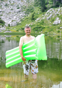 Man on mountain lake ready for swimming