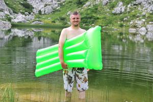Man on mountain lake ready for swimming