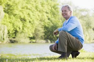 Man outdoors at park by lake smiling