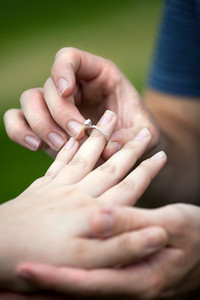 Man placing a diamond engagement ring on the finger of his fiance.  Shallow depth of field with focus on the ring.