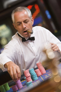 Man placing bet at roulette table in casino