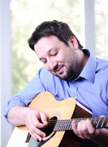 Man playing guitar and relaxing at home