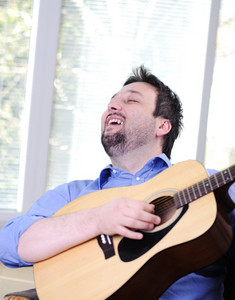 Man playing guitar and singing indoor at sofa
