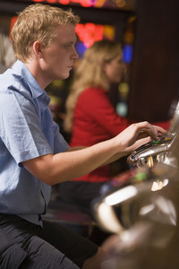 Man playing slot machines in casino