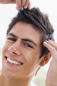 Man playing with hair smiling