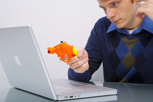 Man pointing gun at laptop