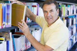Man pulling a library book off shelf