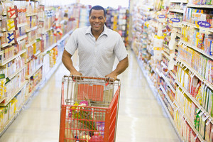 Man pushing trolley along supermarket grocery aisle