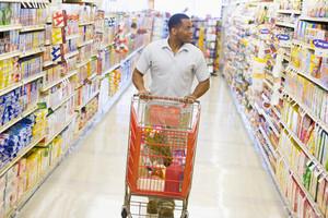 Man pushing trolley along supermarket grocery aisle