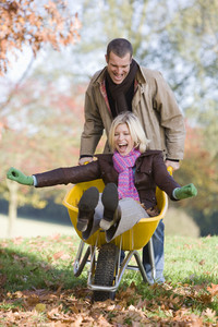 Man pushing wife through autumn leaves in wheelbarrow