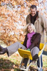 Man pushing woman in wheelbarrow through autumn leaves