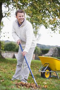 Man raking autumn leaves in autumn garden