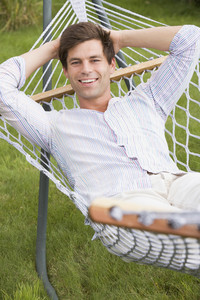Man relaxing in hammock smiling