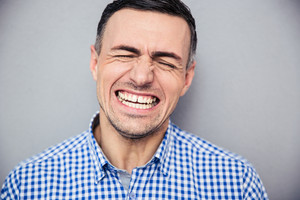 Man screaming over gray wall