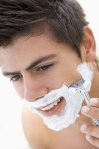 Man shaving and smiling