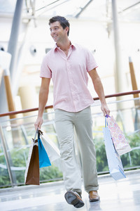 Man shopping in mall carrying bags