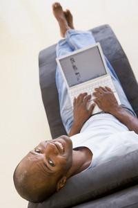 Man sitting in chair using laptop smiling