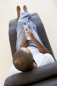 Man sitting in chair using remote control