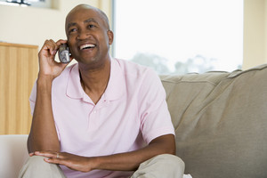 Man sitting in living room using telephone and smiling