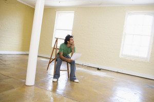 Man sitting on ladder in empty space holding paper thinking