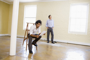 Man sitting on ladder in empty space holding paper with other man behind him