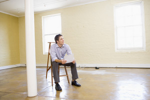 Man sitting on ladder in empty space holding paper