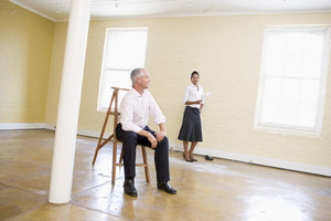 Man sitting on ladder in empty space with woman holding paper