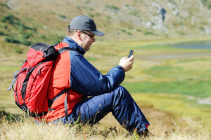 Man sitting on mountain and searching for mobile signal