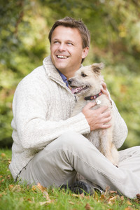 Man sitting outside holding pet dog
