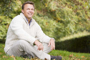 Man sitting outside on grass in autumn landscape