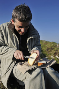 Man slices fresh cheese outdoor in nature