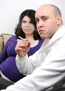 man smoking near pregnant woman
