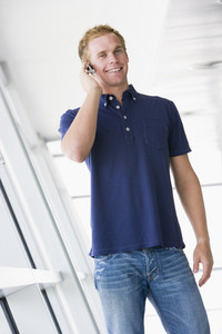 Man standing in corridor wearing headset smiling