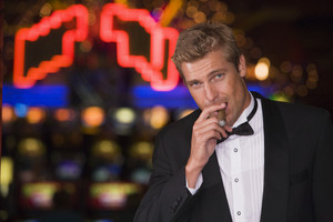 Man standing inside casino smoking cigar