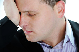 Man suffering from migraine or headache over white