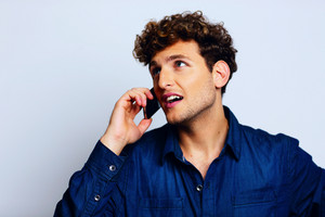 Man talking on a mobile phone and looking shocked