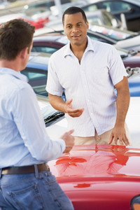 Man talking to car salesman at lot