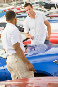 Man talking to car salesman on lot