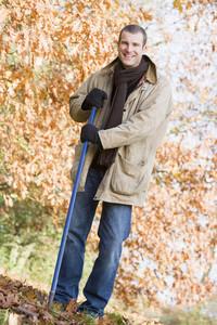 Man tidying autumn leaves in garden
