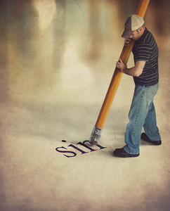Man using a large pencil to erase the word sin.