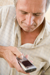 Man using cellular phone indoors