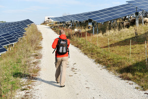 Man walking on a countryside road with solar panels