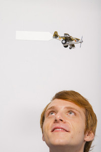 Man watching airplane with sign