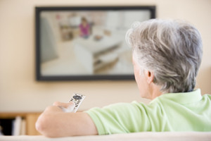Man watching television using remote control