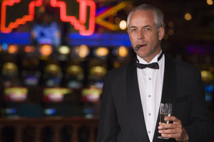 Man wearing tuxedo in casino smoking cigar