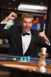 Man winniing at roulette table in casino