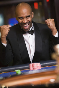Man winning at roulette table in casino