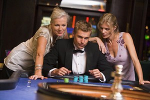 Man with glamorous women in casino at roulette table