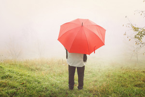 Man with red umbrella on foggy field